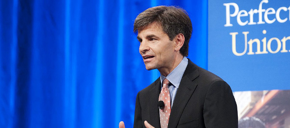 George Stephanopoulos speaking in front of a blue background