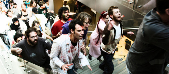 shoppers in zombie costumes and makeup ascending stairs at an Apple store