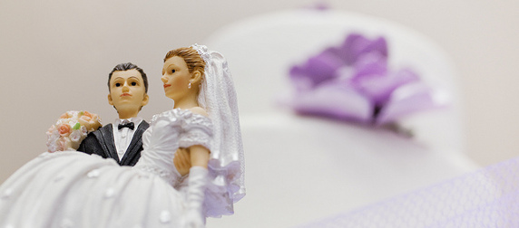 wedding topper with groom carrying the bride, shot in front of an out-of-focus white wedding cake with purple accents