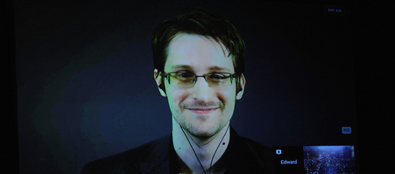 Edward Snowden, wearing earbuds, appearing on a projection screen