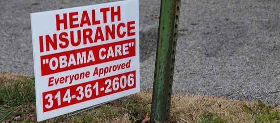 yard sign that reads Health Insurance, Obama Care, Everyone Approved, and a phone number