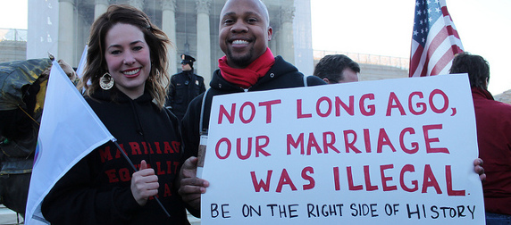interracial couple holding a protest sign that reads, 'Not Long Ago, Our Marriage Was Illegal. Be On The Right Side Of History'