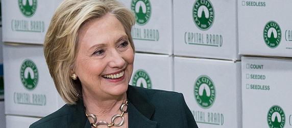Hillary Clinton, smiling, in front of white boxes labeled 'Capital Brand' with a green logo