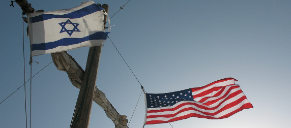 Israeli and American flags flying on either side of a ship's mast, viewed from below