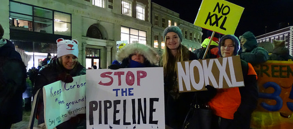 protesters holding anti-Keystone XL Pipeline signs