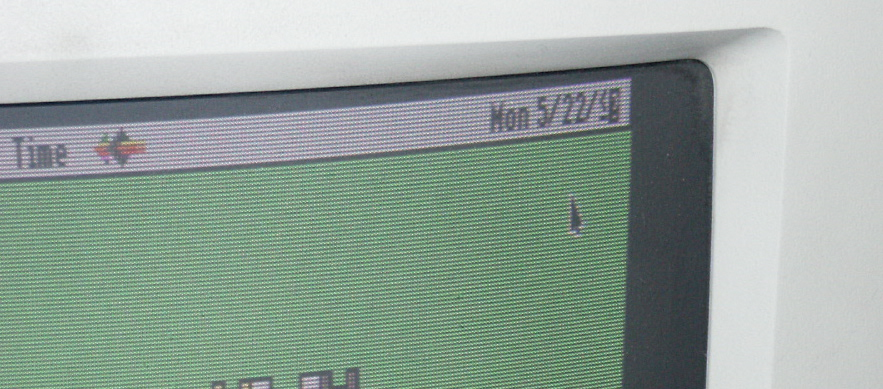 detail of a CRT Macintosh monitor with the date 5/22/<? and a cursor on a green background