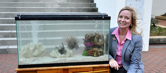 State Rep. Holly Raschein posing next to an aquarium with lionfish