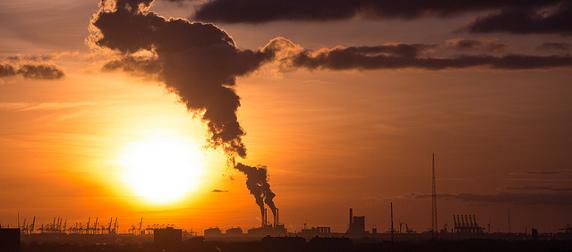 factory smokestack seen against a setting sun