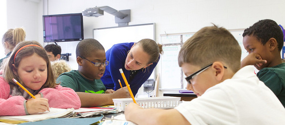 teacher working with elementary-aged students writing at a table
