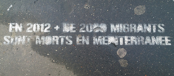 spray-painted text reading 'En 2012, + de 2000 migrants sont morts en Méditerranée'