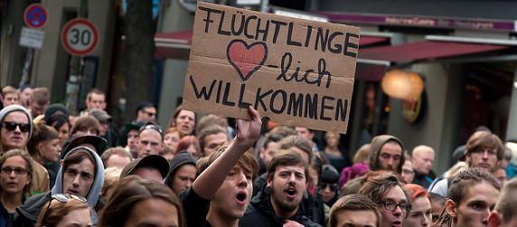 protestors, one holding a cardboard sign that reads 'fluchtlinge herzlich willkommen'