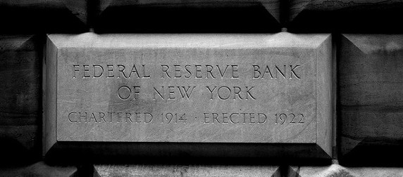 black and white image of a brick, engraved with 'Federal Reserve Bank of New York, Chartered 1914, Erected 1922'