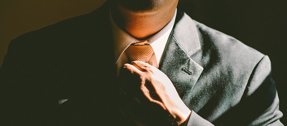 close-up of a person in a suit adjusting a necktie