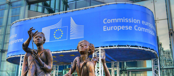 statue of children outside the Berlaymont building in Brussles, with a European Commission banner in the background