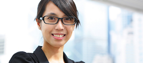 businesswoman with glasses against a pale, out-of-focus background