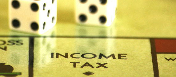 dice on a Monopoly board above the Income Tax space