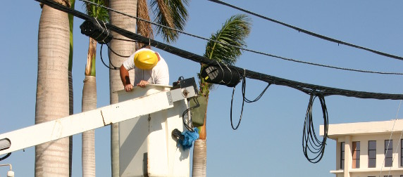 electric company worker in bucket truck inspecting power lines