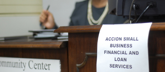 printed sign reading Accion Small Business Financial and Loan Services, taped to the edge of a desk