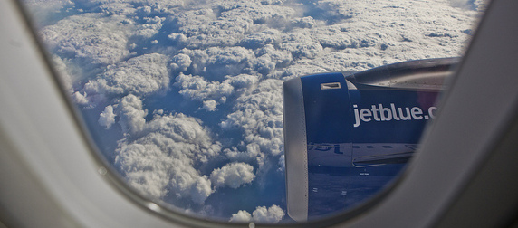 view out window of a JetBlue plane in flight, clouds in background