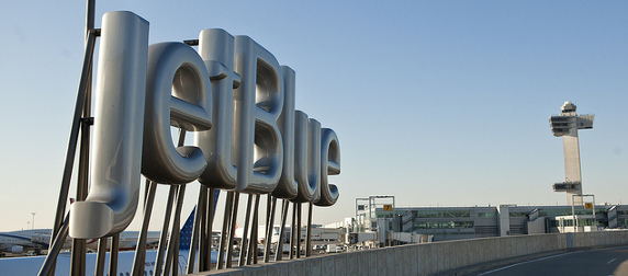 outdoor JetBlue sign with air traffic control tower in background