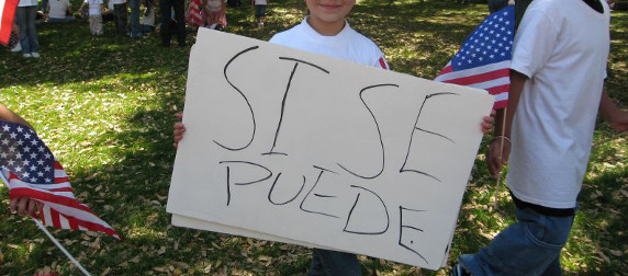 hand-drawn poster reading SI SE PUEDE, held by a child, with American flags in the background