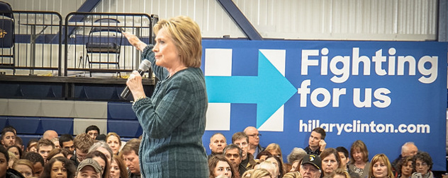 Hillary Clinton speaking to a crowd in front of a banner that reads Fighting For Us hillaryclinton.com