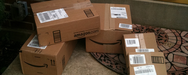 stack of Amazon delivery boxes on a home's doorstep