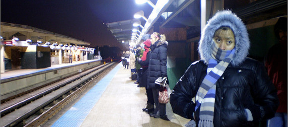 commuters dressed for cold weather waiting on a train platform in Chicago