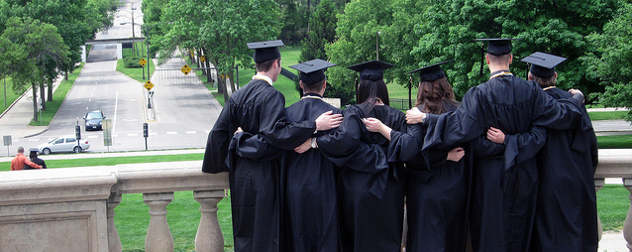 students dressed for graduation, standing together facing away from the camera