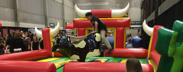a rider attempting to mount an indoor mechanical bull at CVX Live