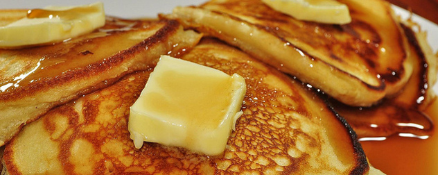 close-up of pancakes with pats of butter, drenched in maple syrup