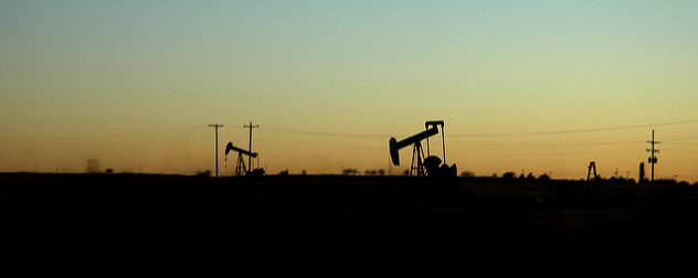 Sunset with an oil well silhouetted against the horizon