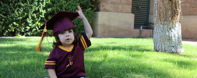 toddler wearing a mortarboard and ASU jersey, seated on grass