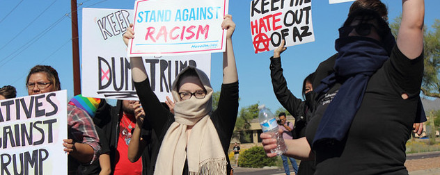 protesters holding signs that include 'Stand Against Racism' and 'Keep Hate Out of AZ'