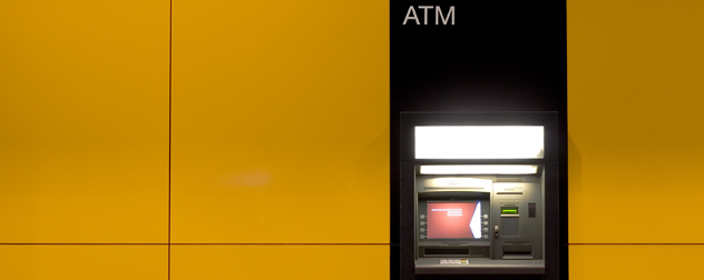 ATM with no bank affiliation embedded in a yellow wall