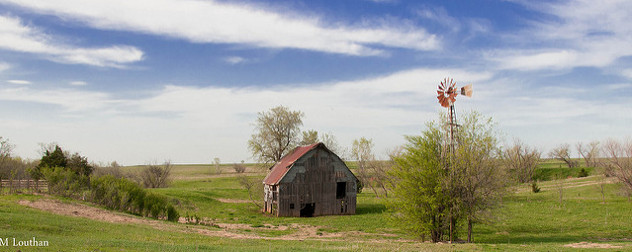 an abandoned barn and weathervane against a rural landscape in summer