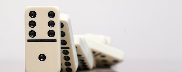 line of falling dominoes against a white background