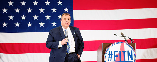 Chris Christie with a microphone in front of an American flag, a podium with the banner #FITN on his left