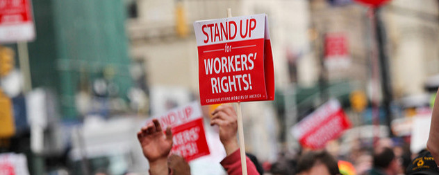 a protest sign that reads 'Stand Up for Workers' Rights! Communications Workers of America' held aloft over a crowd