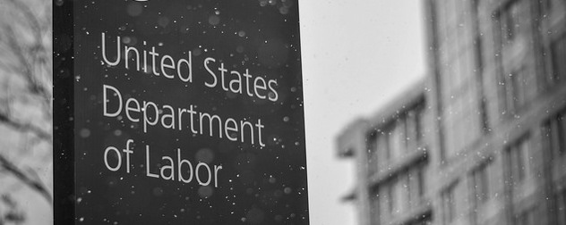 black-and-white image of a sign reading United States Department of Labor in the snow, Labor Department out of focus in the background