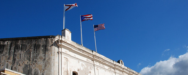 Cross of Bergundy, Puerto Rican and US flags flying over the Castillo de San Cristobal's facade