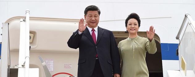 Xi Jinping and Peng Liyuan waving from the door of an airplane