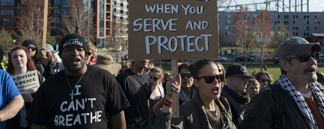 protesters with signs reading No Justice, No Peace; I Can't Breathe; and a partial sign reading When You Serve and Protect