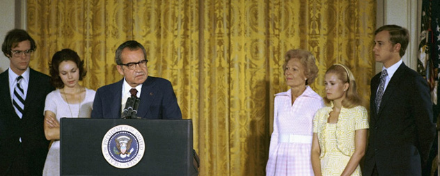 Richard Nixon delivering remarks at a White House podium, surrounded by his wife, daughters and sons-in-law