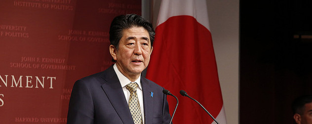 Shinzo Abe speaking in front of a Japanese flag at the John F. Kennedy School of Government