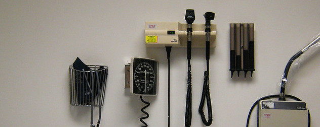medical instruments on wall, including a blood pressure monitor, an otoscope and an ophthalmoscope