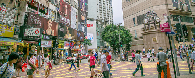 shoppers walk among storefronts and billboards in Hong Kong