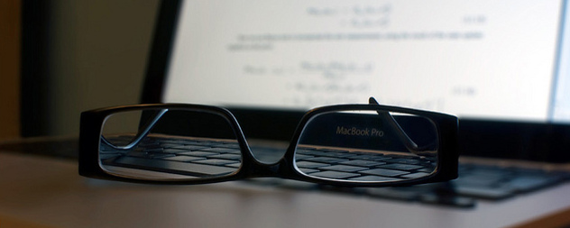 reading glasses resting on a MacBookPro keyboard, the screen illuminated but out of focus