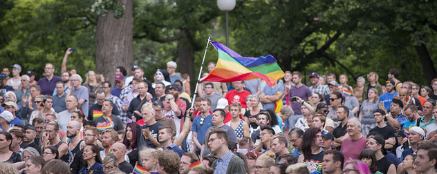 crowd gathered in a park, a rainbow flag held aloft in the center