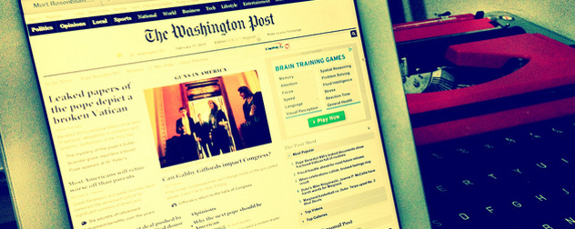 The Washington Post homepage displayed on an iPad, a typewriter in the background